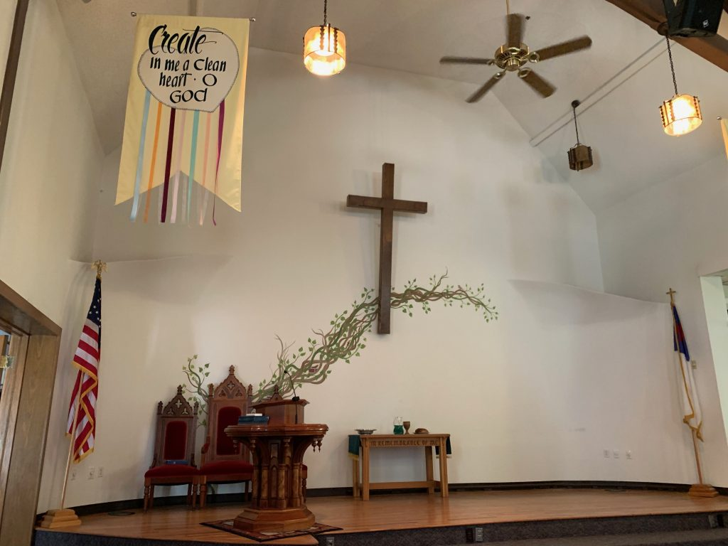 A cross hangs on a white wall with a painting of a vine behind it.