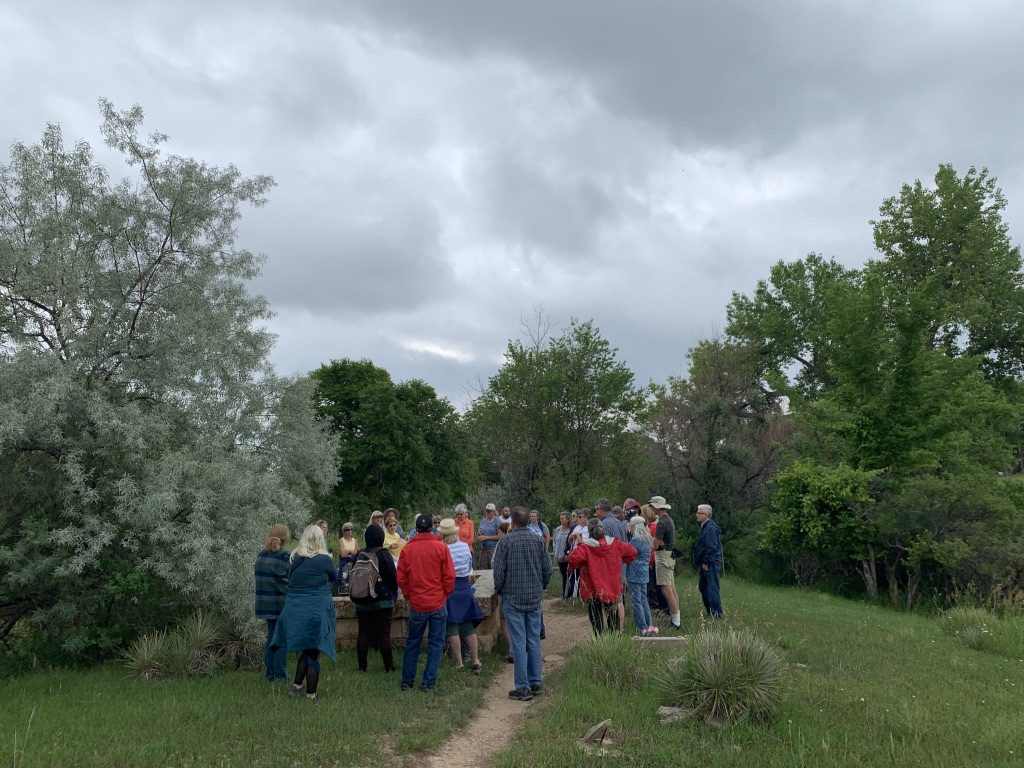 A crowd of people stand in a clearing surrounded by trees. The grass is green and only a few headstones can be seen.