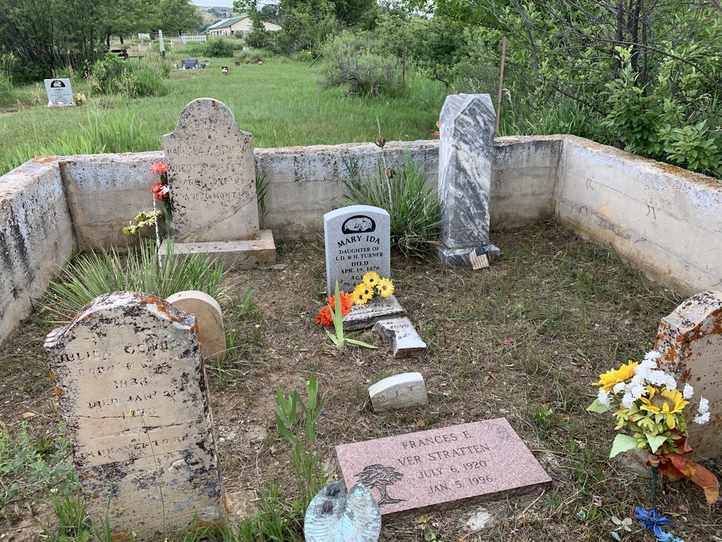 Several older and newer gravestones stand surrounded by a stone or cement wall in the cemetery.