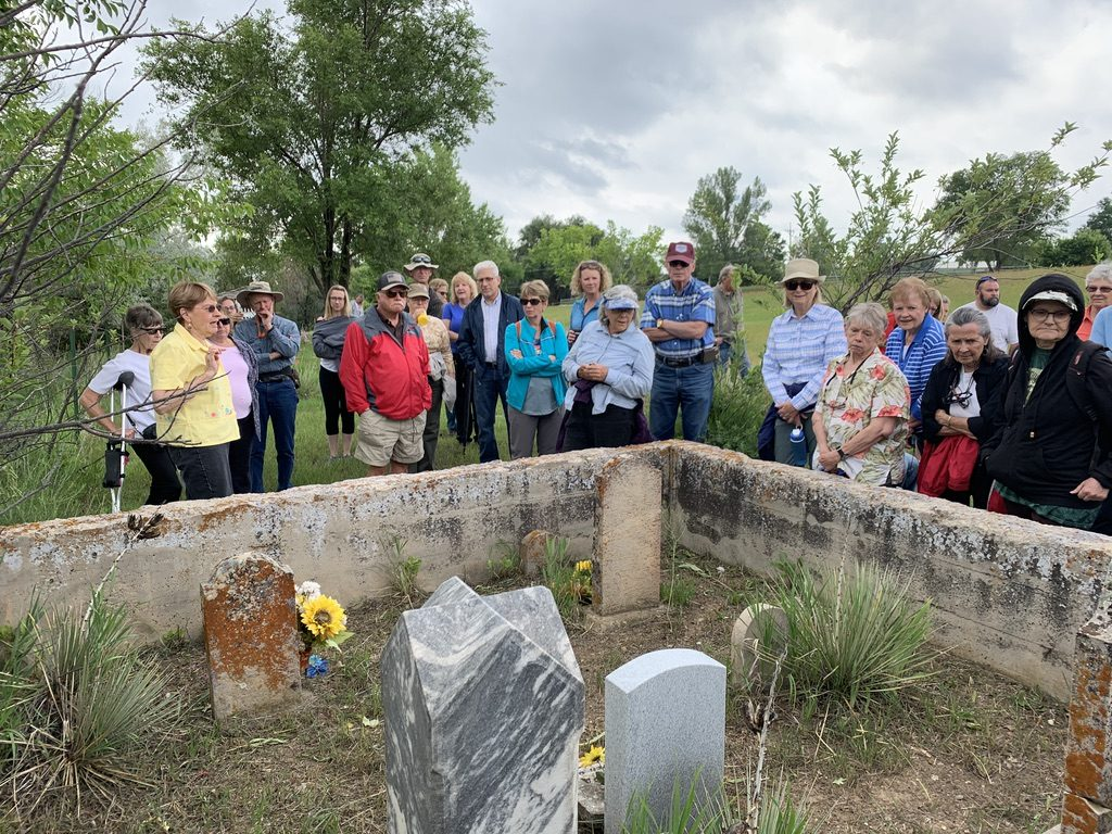 Judy stands surrounded by the tour group with headstones in the foreground.