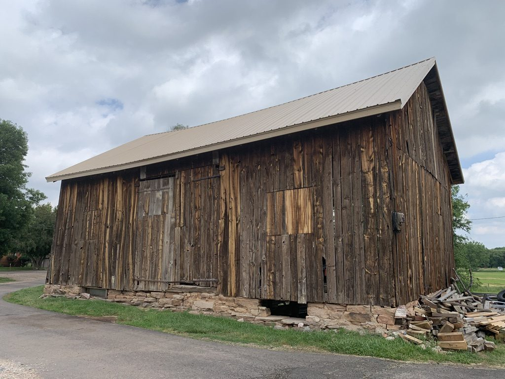 A wood frame barn stands precariously over a cut stone foundation.