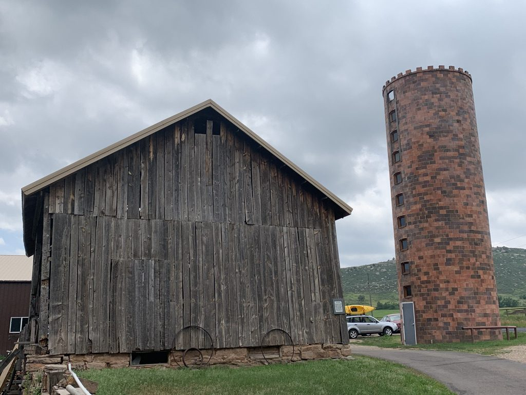 A wood frame barn stands at left with a brick crenelated silo to the right.