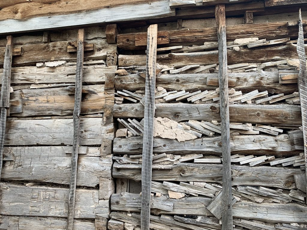 Wood beams to the left form a log cabin with an addition consisting of beams and boards wedged together.