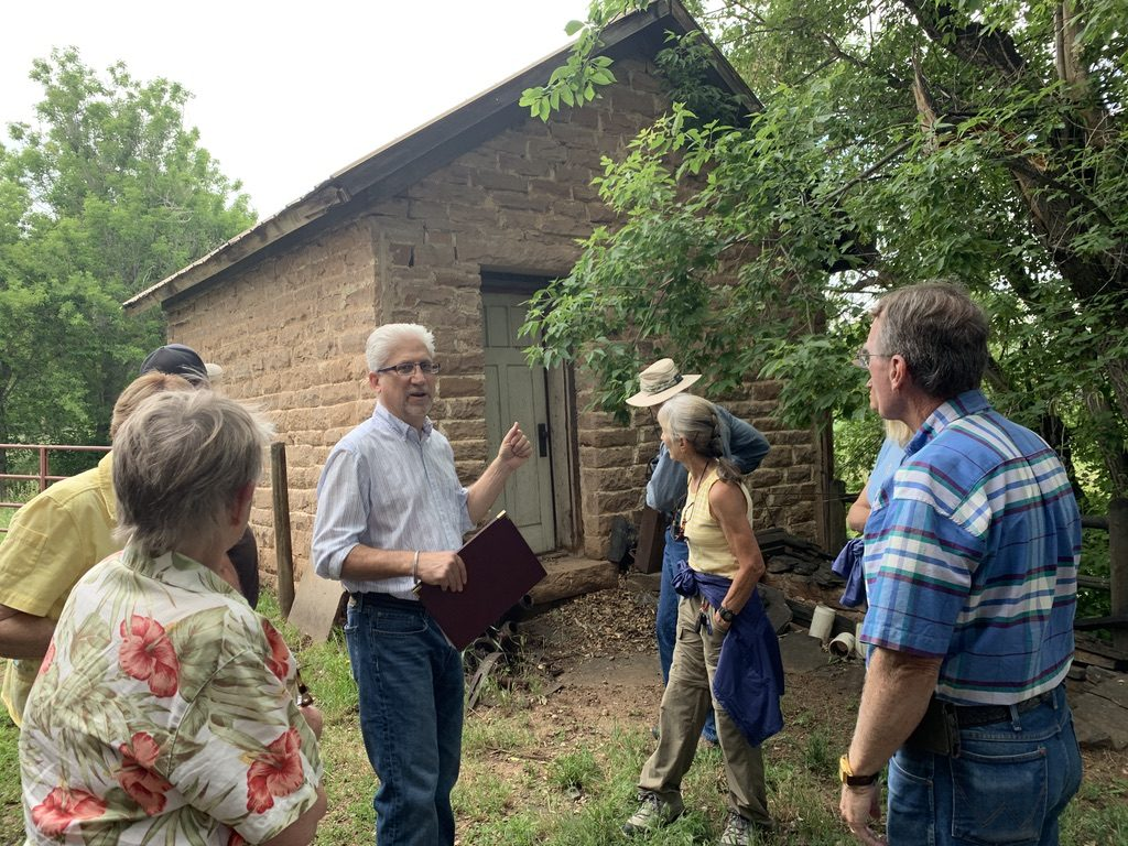Ron Sladek points to a stone building with a wooden door.