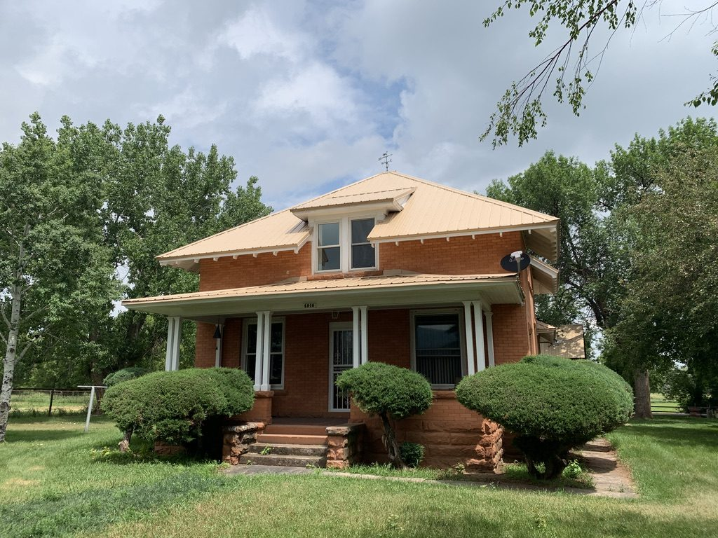 A four square brick house with a hipped roof and a wide, deep porch stands behind trimmed bushes.